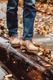 Hiker walking in boots closeup. Hiker wearing boots walking across river in autumnal forest. Footwear on man's legs closeup outdoor. Male seasonal shoes Stock Photos