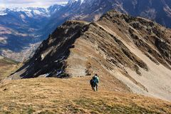 Hiker walking down mountain ridge royalty free stock photos