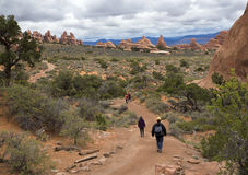 Hiker walking down a trail at the Devils Garden at Arches National Park in Moab Utah. Stock Photo