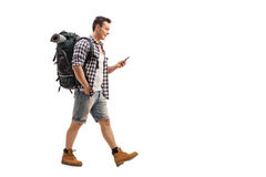 Hiker walking and looking at a mobile phone stock photo