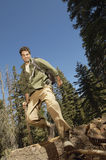 Hiker Walking Over Log In Forest Stock Photo