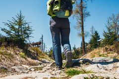 Hiker walking on path in the mountains Stock Image