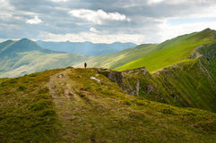 Hiker walking on ridge path. A hiker walking through a beautiful mountain landscape Stock Photography