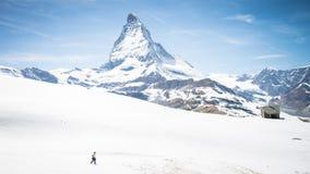 Hiker walking on snow towards Matterhorn Mountain with white snow and blue sky in Zermatt cit Stock Photo