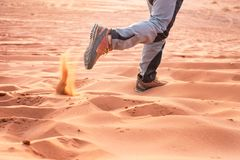 Hiker walking throught sandy desert. Traces in sand. Focus on a man legs. Tourist in a desert. Sandy background. Hiker walking throught sandy desert. Traces in Royalty Free Stock Photo