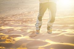 Hiker walking throught sandy desert. Traces in sand. Focus on a man legs. Tourist in a desert. Sandy background. Hiker walking throught sandy desert. Traces in Royalty Free Stock Photos