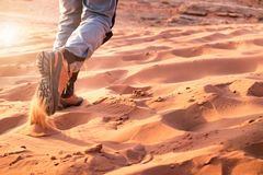 Hiker walking throught sandy desert. Traces in sand. Focus on a man legs. Tourist in a desert. Sandy background. Hiker walking throught sandy desert. Traces in Stock Photos