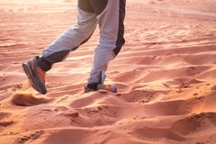 Hiker walking throught sandy desert. Traces in sand. Focus on a man legs. Tourist in a desert. Sandy background. Hiker walking throught sandy desert. Traces in Stock Photo