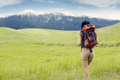 Hiker walking toward the mountain Stock Photo