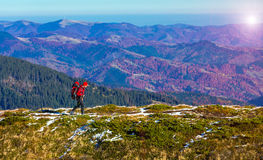 Hiker walking on Trail with Backpack Mountains View Sun Shining. One Male Hiker walking on Trail with Backpack panoramic Mountains View bright Autumnal Colors Stock Photo