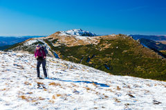 Hiker walking up on Snow Slope Mountains View Royalty Free Stock Photo