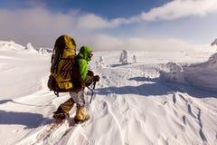 Hiker walking in winter mountains Royalty Free Stock Image