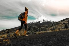 Hiker walks on the slope of volcano. Woman enjoys the trail with views of the volcano of Osorno, Chile royalty free stock photos