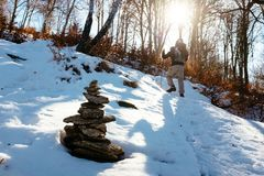 Hiker walks in snow-covered mountain. Hiker with snowshoes walks in the snowy woodland on a bright morning Royalty Free Stock Photo