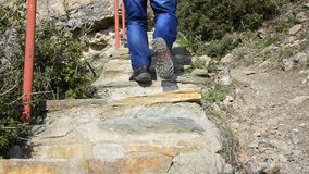 Hiker walks up stone stairs Stock Photo