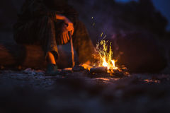Hiker warms their feet next to a campfire at dusk camping in the woods Royalty Free Stock Images