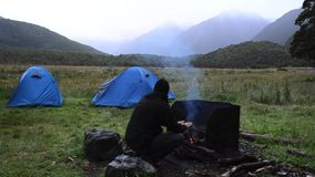Hiker warms up over an outdoor campfire stock video