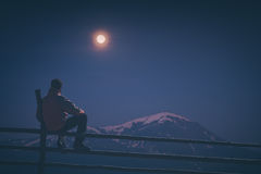 Hiker watch the moon rising. Instagram stylization. A hiker sitting on a wooden fence and enjoy rising of full moon above the high mountain covered with snow Stock Images