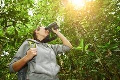 Hiker watching through binoculars wild birds in the jungle. Bird watching tours Royalty Free Stock Images