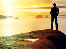 Hiker watching to autumn  Sun at horizon . Beautiful moment the miracle of nature. Colorful mist in valley. Man stands alone Royalty Free Stock Photography