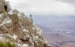Hiker waving on Mount Liberty. Hiker waving his arms about  while standing on a precarious rocky ledge close to the summit of Mount Liberty, in White Mountains Stock Image