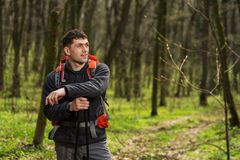 Hiker wearing hiking backpack and jacket on hike in forest. Man using hiking sticks poles outdoors in woods. Male hiker standing looking away Royalty Free Stock Image
