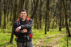 Hiker wearing hiking backpack and jacket on hike in forest. Man using hiking sticks poles outdoors in woods. Male hiker standing looking away Royalty Free Stock Photography