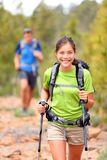 Hiker woman. Hiking asian women walking with hiking poles and hiking backpack smiling happy outdoors in nature. Hiker in background Royalty Free Stock Photos