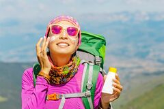 Woman applying sun cream to protect her skin from dangerous uv sun rays high in mountains. Travel healthcare concept
