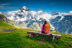 Hiker woman with backpack relaxing on the bench, Grindelwald, Switzerland royalty free stock images
