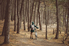 Hiker woman with bike in the forest Stock Photos