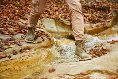 Hiker woman crossing a river, view of legs Royalty Free Stock Image