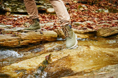 Hiker woman crossing a stream, view of legs Royalty Free Stock Photography