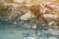 Hiker woman drinking a water from creek Royalty Free Stock Images