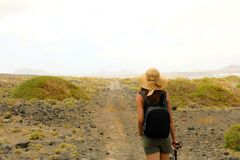 Hiker woman exploring dry region of Lanzarote Island. Young female backpacker with straw hat walking in desolate path of Lanzarote. Canary Islands Stock Photos