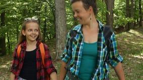 Hiker woman and girl walking among trees. Hikers enjoy walking in forest - woman and girl walking downhill among trees stock video footage