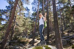 Hiker woman on a great rock in forest with victory sign in hand. Hiker sport woman standing on a great rock in the forest, waving with victory sign in hand, in Stock Photography