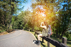 Hiker woman look binoculars on the road. In the forest Royalty Free Stock Images