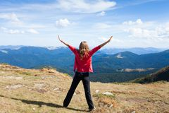 Hiker woman on a peak mountain with raised hands Stock Images