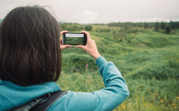 Hiker woman photographs the summer landscape Royalty Free Stock Image