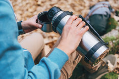 Hiker woman pours tea from thermos to cup outdoor Stock Photography