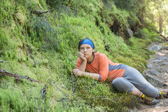 Hiker woman relaxing, lying on the green moss, looking at camera Stock Photos
