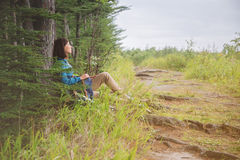 Hiker woman resting near the tree in forest Royalty Free Stock Photos