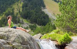 Hiker woman rests on a rock in the mountains Stock Photos