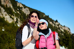 Hiker woman showing something to her daughter in the mountain Stock Image