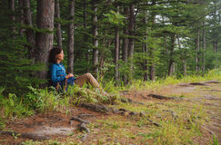 Hiker woman sitting near the tree in forest Royalty Free Stock Photos
