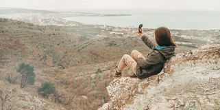 Hiker woman sitting on peak of mountain with a compass Royalty Free Stock Photos