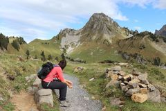 Hiker (woman 20-25) sitting on rock. Next to pathway with scenic mountain view royalty free stock photos