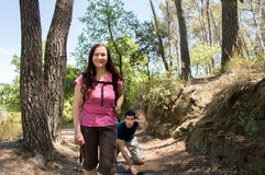 Hiker woman smiling on the forest and man has an accident Royalty Free Stock Image