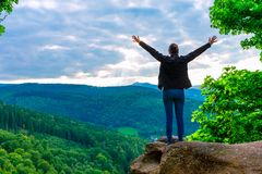 Hiker woman standing with hands up achieving the top. Admiring mountain landscape. Epic shot of hiking with cloudy sky, freedom success concept royalty free stock images